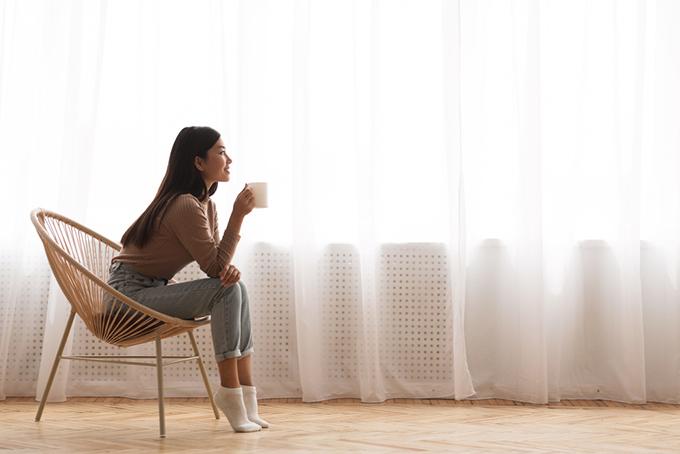 お部屋で椅子にすわってお茶する女性
