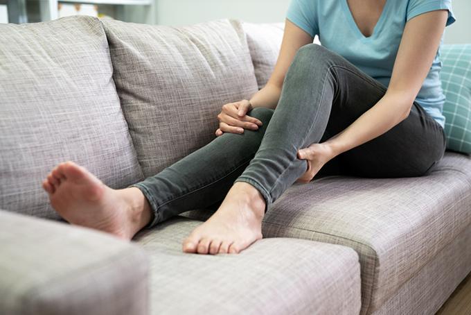 足を押さえる女性の画像