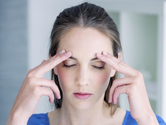 眉からと頭頂部に向けて指を動かす女性