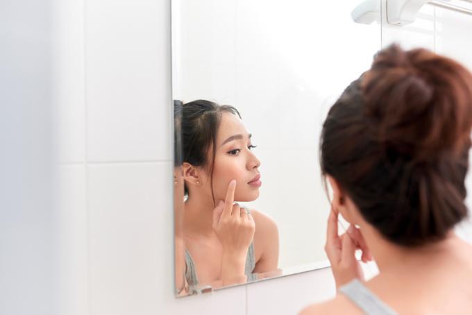 鏡を見ながらほほに手をやる女性の画像