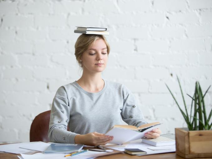 頭に本をのせて正しい姿勢を保つ女性