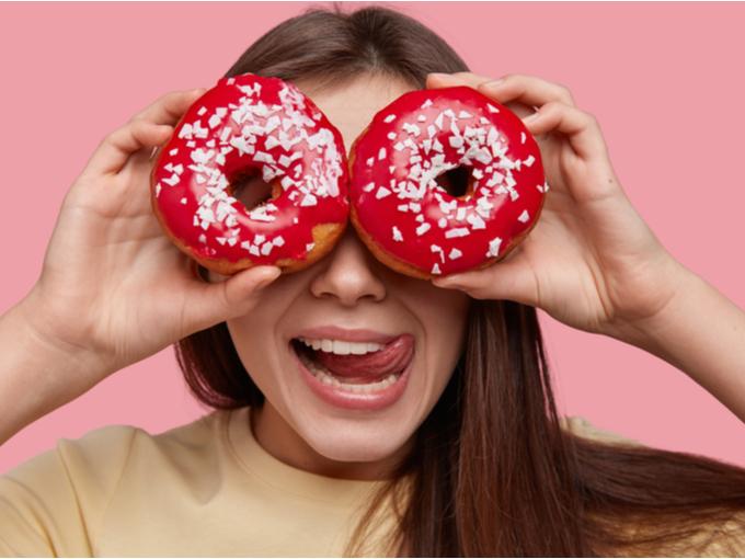 顔の前にドーナツを掲げる女性
