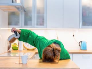 疲れ過ぎてカップの外にコーヒーを注いてしまう女性