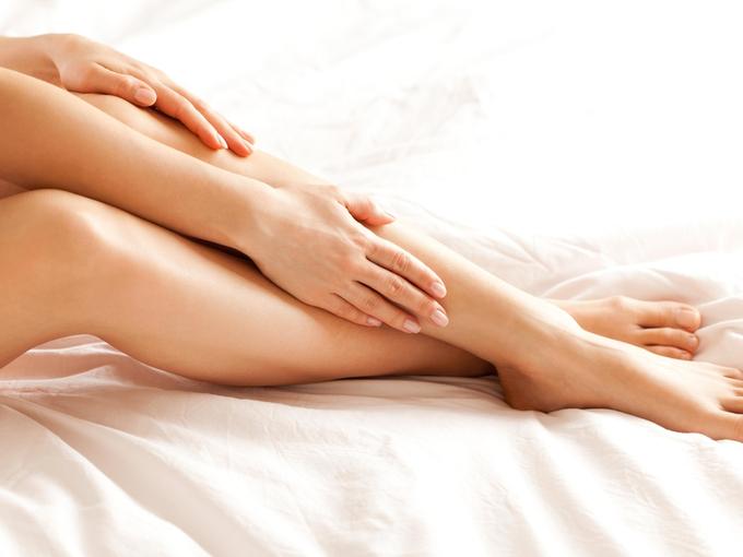足の肌をさわっている女性