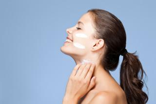 クリームを塗る女性の横顔の画像