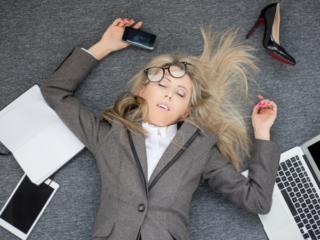 オフィスの床に寝ている疲労困憊の女性