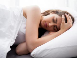 頭痛がつらくてベッドから起きられない女性