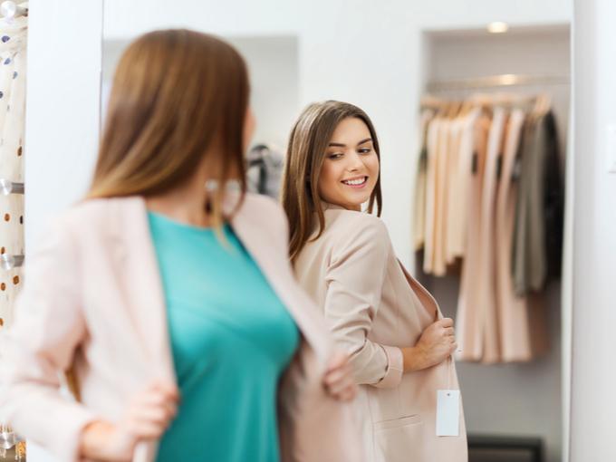 鏡を見て、服が似合っているかどうかたしかめている女性