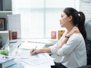 仕事中に肩こりを気にする女性