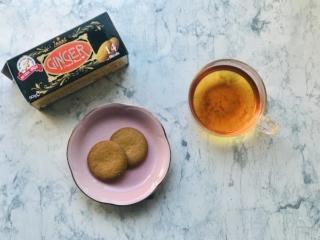 お皿に盛ったジンジャービスケットとカップに注がれた紅茶