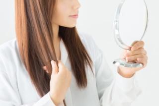 鏡を見ながら髪の毛を触る女性