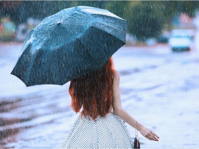 雨の中傘をさす女性のうしろ姿
