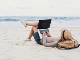 浜辺でくつろぎながらパソコンで仕事する女性