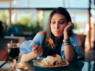 カロリーを気にしながら食事をする女性