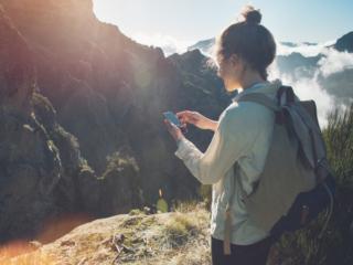山でスマートフォンを見ている女性の画像