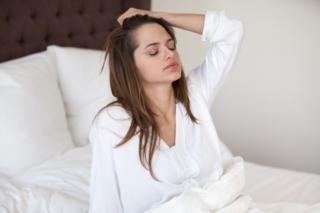 ベッドで体を起こして額に手をやる女性の画像