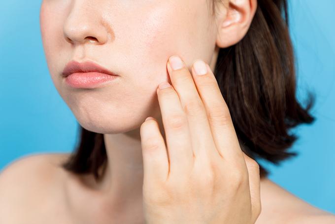 顔の肌をさわっている女性