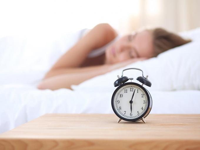 覚まし時計と安眠する女性の様子
