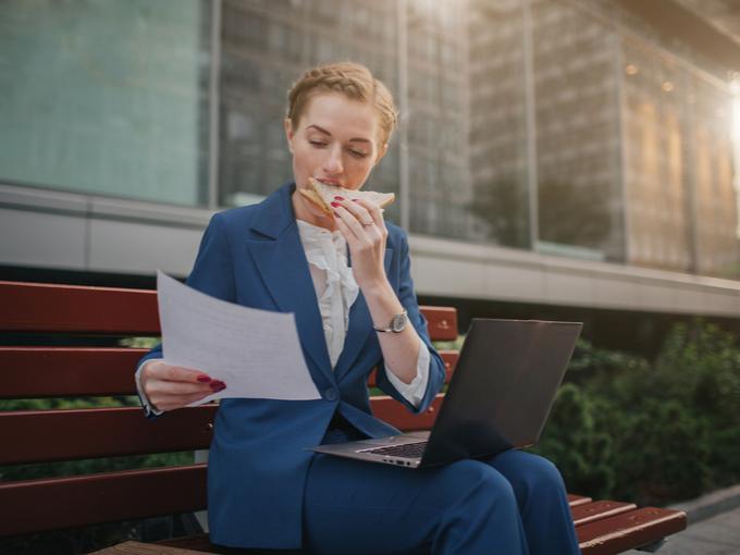 ベンチでサンドウィッチを食べながら仕事をする女性