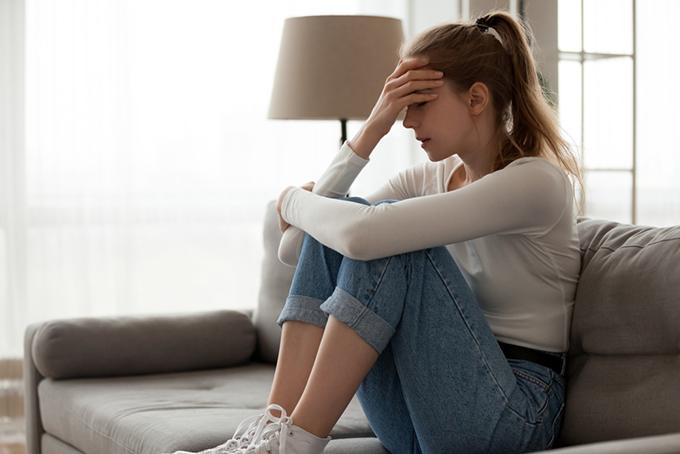 ソファの上で頭を押さえて悩んでいる女性のイメージ画像