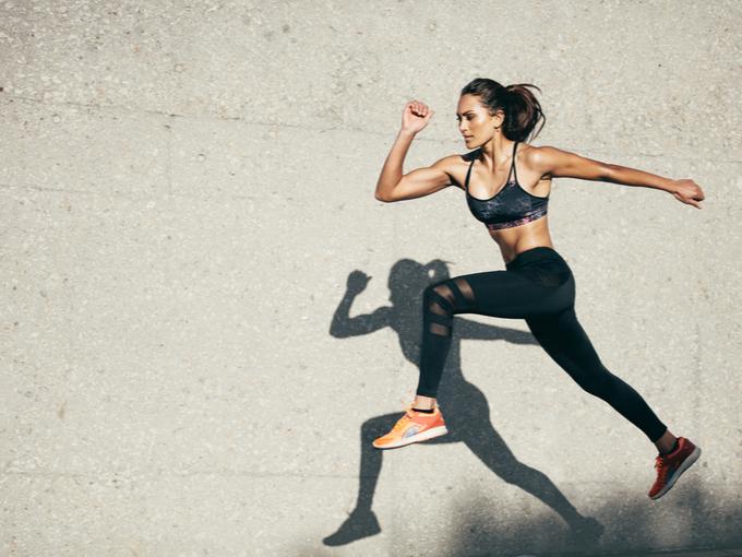 脚と腕のスイングを大きくして走る女性