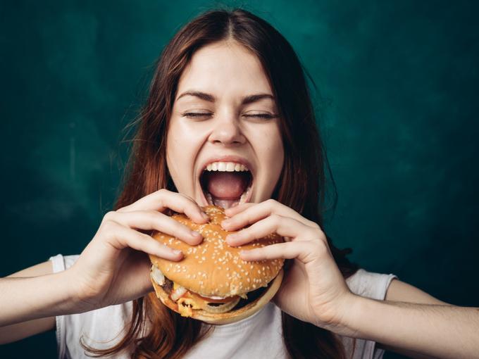 大きなハンバーガーを食べる女性