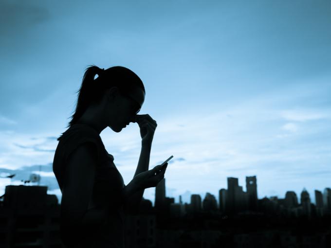 頭痛を抱えながらスマホを見る女性のシルエット