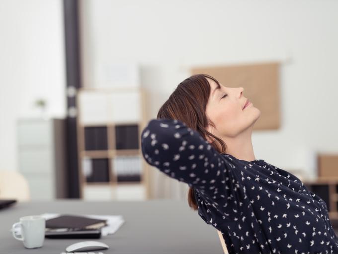 仕事の休憩中に首を伸ばす女性