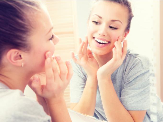鏡の前で肌の調子を見る女性