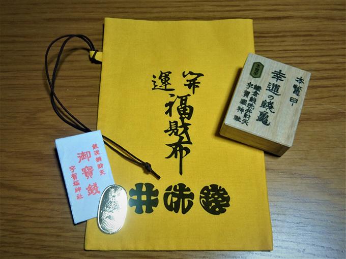 黄色い巾着、御賽銭、銭亀の箱の写真