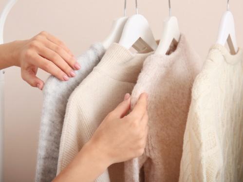 白いニットを選ぶ女性の手