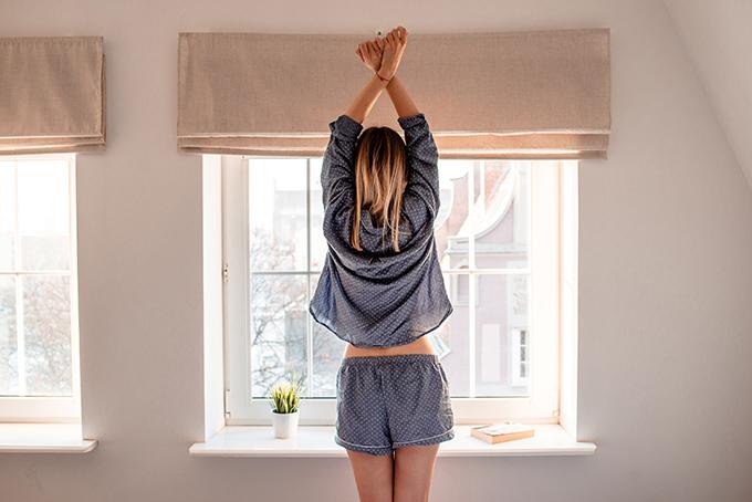 窓辺で伸びをする女性