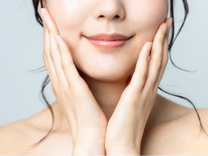 顔の肌を保湿する女性