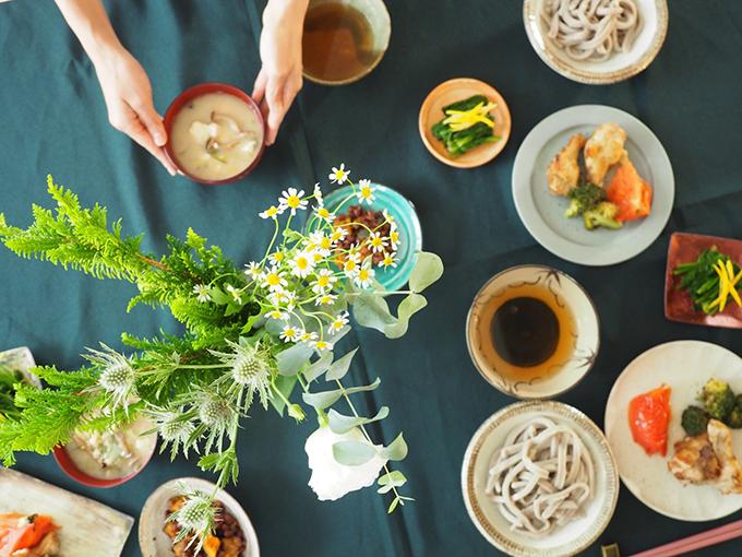 手を添えた味噌汁といくつかのお皿とお花の俯瞰の画像