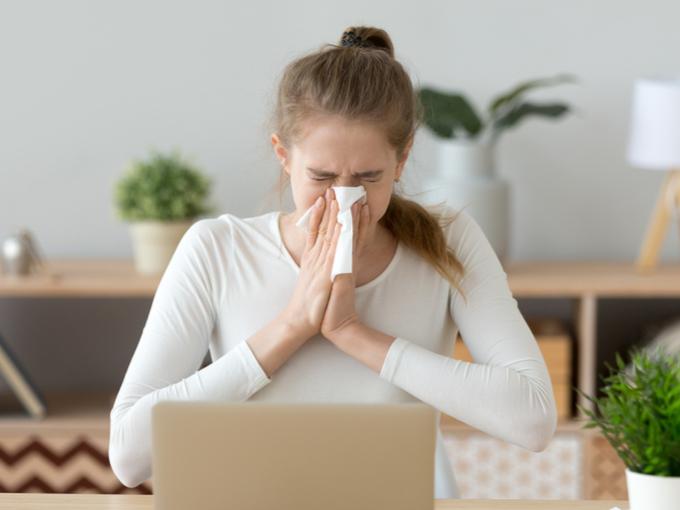 PC作業中に鼻をかんでいる女性