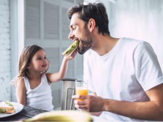 パンを父親に食べさせる女の子