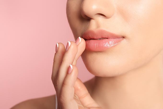 唇にふれる女性の手の画像