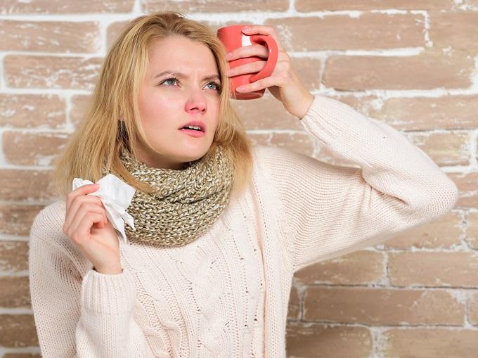 マグカップを額に当てる女性