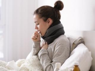 ベットで咳をしている女性