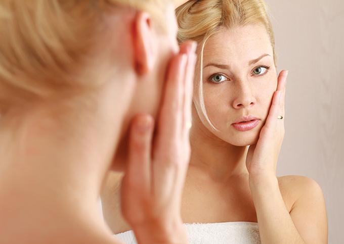肌に手を当てて自分の顔を見ている鏡ごしの女性