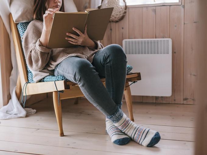ヒーターのそばで椅子に座って本を読む女性