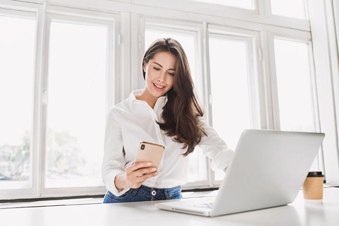 パソコンを前にしてスマホを見ている女性の画像