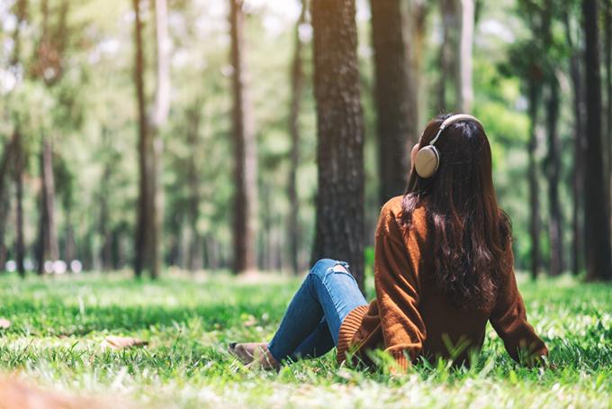 自然の中でヘッドホンをしている女性の画像