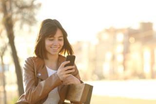 スマホに向かって微笑んでいる女性の画像