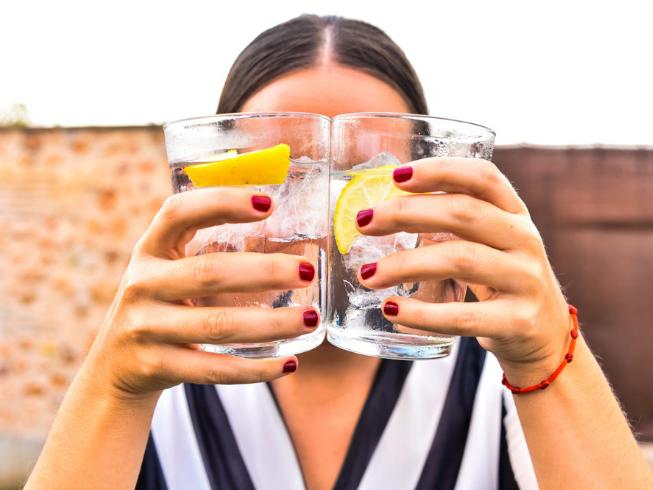 女性が顔の前で2つのグラスを合わせている画像