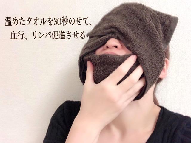 顔を蒸しタオルで温めている