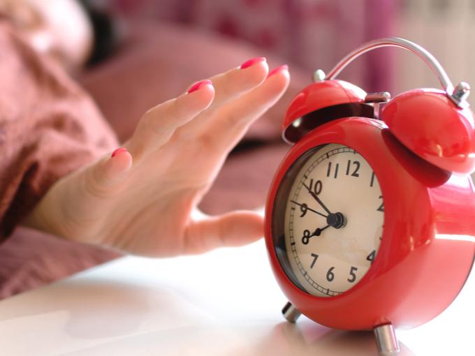 目覚まし時計に手を伸ばす女性の写真