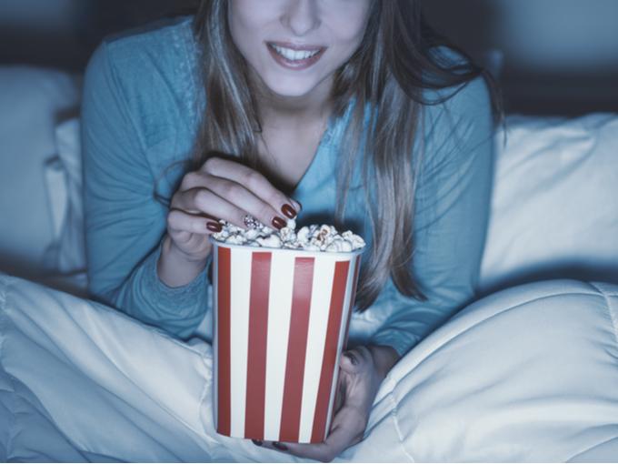 夜中にベッドでポップコーンを食べる女性