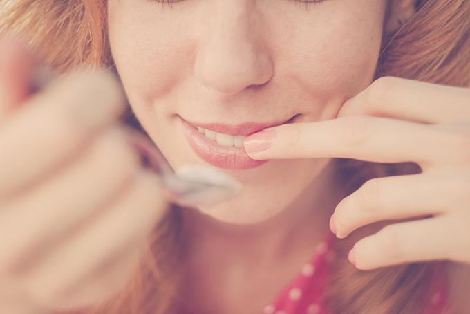 唇にふれる女性の顔半分の画像