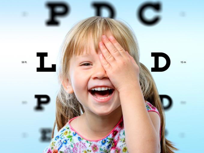 片目を隠して視力を確認する女の子